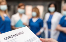 A group of doctors with face masks talking about corona virus on conference.